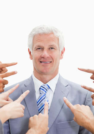 criticize: Smiling businessman with fingers being pointed at him from many directions against white background LANG_EVOIMAGES