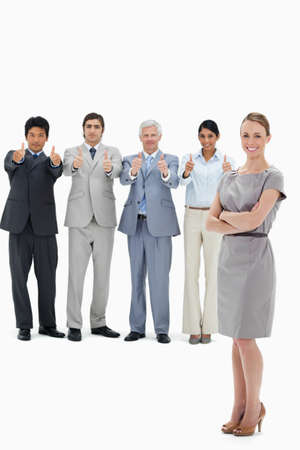 thumbsup: Multicultural business team with their thumbs-up with a smiling woman with her arms folded in foreground against white background