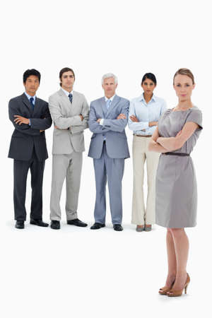 arms folded: Multicultural business team with their arms folded with a woman in foreground against white background