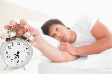 awoken: Close up and focus on the alarm clock which the half awake man is turning off with his hand.