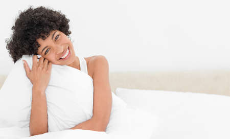 head tilted: Portrait of a frizzy woman hugging her pillow in her white bed