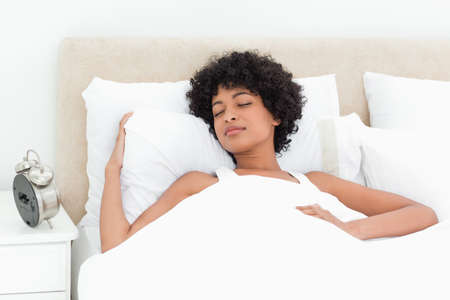 peacefully: Woman with curly haired sleeping peacefully in a white bed LANG_EVOIMAGES
