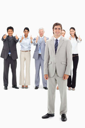 thumbsup: Multicultural business team with their thumbs-up focus on a smiling man in foreground against white background