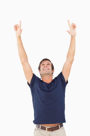 arms above head: Smiling man raising his arms above his head against a white background