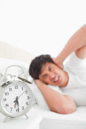 awoken: The focus is on the ringing alarm clock as the man in the background covers his ears in anger. LANG_EVOIMAGES
