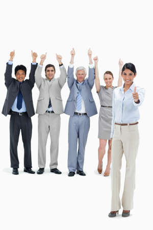 thumbsup: Multicultural business team raising their arms and giving the thumbs-up with a woman in foreground against white background