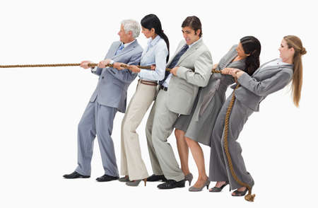 tugging: Business people pulling a rope against white background