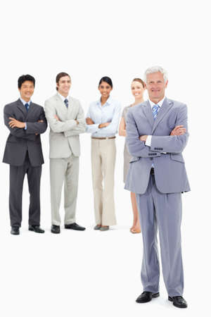 arms folded: Smiling multicultural business team with their arms folded focus on a mature man in foreground LANG_EVOIMAGES