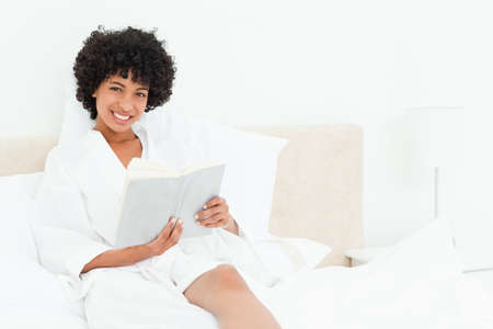 frizzy: Frizzy haired woman smiling in a dressing gown reading a book LANG_EVOIMAGES
