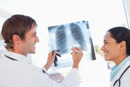 chest xray: Two doctors working on a chest x-ray while smiling and looking at each other
