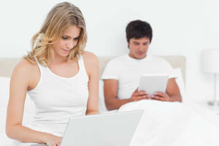 pcs: The man and woman at opposite ends of the bed smiling using types of pcs