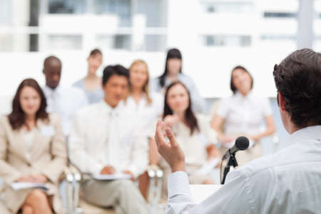 brown haired: Brown haired businessman gesturing while giving a speech to his colleagues LANG_EVOIMAGES