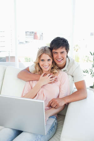 looking ahead: A man holds onto the woman as they use the laptop looking ahead and smiling.