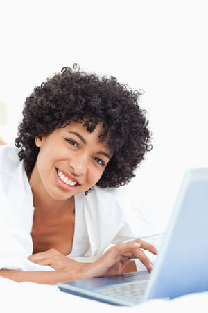 head tilted: Portrait of a smiling woman using a laptop while lying on the belly
