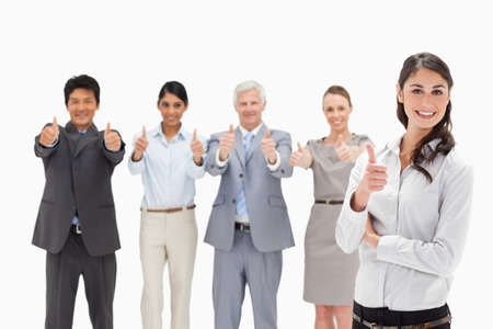 thumbsup: Close-up of a smiling multicultural business team with their thumbs-up focus on a woman in foreground LANG_EVOIMAGES