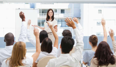 arms above head: Audience watch a businesswoman as they raise their arms above their head