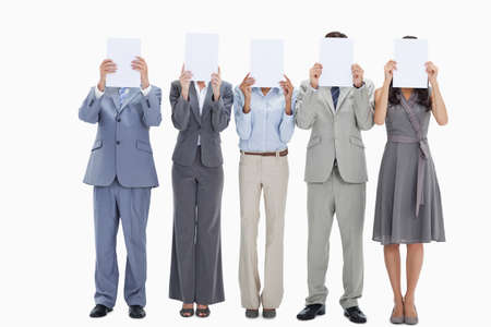placards: Five business people hiding their faces behind small white placards against white background