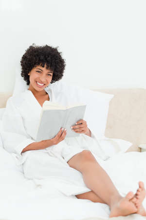 frizzy: Happy frizzy haired woman in a dressing gown reading a book