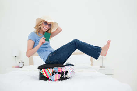 balances: A woman is laughing as she wears glasses and hat, as she balances on her suitcase on the bed. LANG_EVOIMAGES