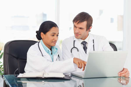 explanations: Doctor pointing at the screen of the laptop while giving explanations to her colleague