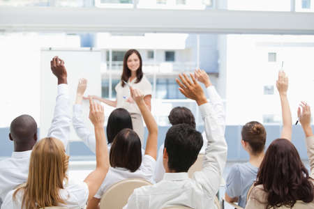 they are watching: Audience raise their arms while they are watching a businesswoman