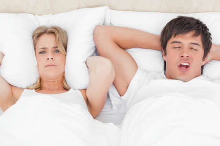 drown: A woman with a pillow over her ears is trying to drown out the mans snoring. LANG_EVOIMAGES