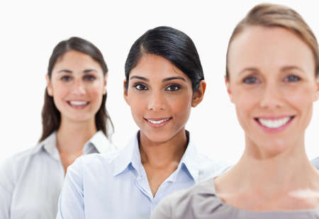 single line: Close-up of smiling businesswomen in a single line with focus on the middle person against white background LANG_EVOIMAGES