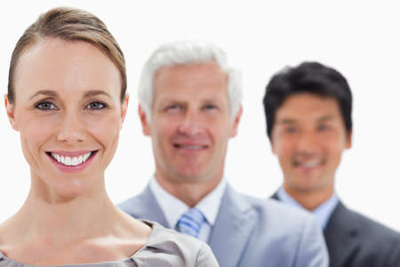 single line: Close-up of smiling business people in a single line with focus on the woman against white background LANG_EVOIMAGES