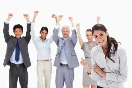 clenching: Successful business team with focus on a smiling woman clenching her fist in foreground