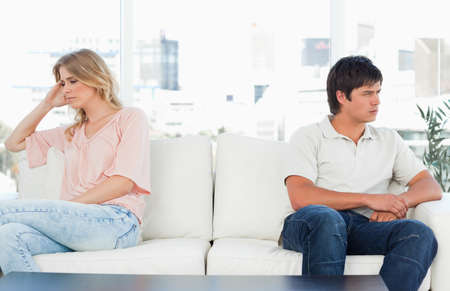agitated: A man and woman sitting away from each other, both looking upset and annoyed.
