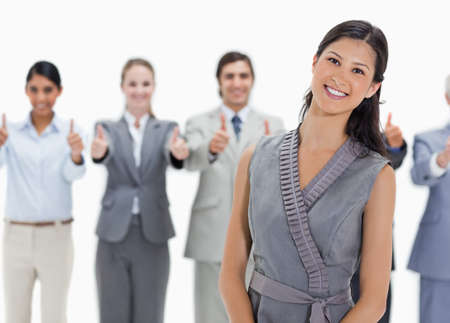 thumbsup: Woman with a business team behind her with their thumbs-up against white background