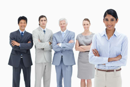 arms folded: Multicultural business team with their arms folded with a woman smiling in foreground against white background