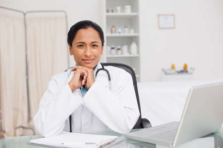 practitioner: Practitioner sitting with hands crossed while placing her elbows on the desk