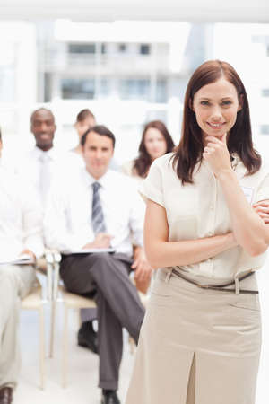 brown haired: Brown haired businesswoman holding her hand against her chin while standing in front of her colleagues