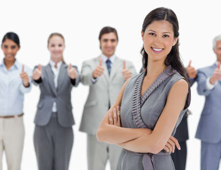 team from behind: Smiling woman with a business team behind her with their thumbs-up against white background
