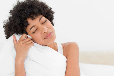 head tilted: Young frizzy haired woman hugging her pillow against white background