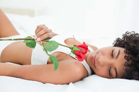 frizzy: Frizzy haired woman lying on her bed with a rose in a bright room LANG_EVOIMAGES