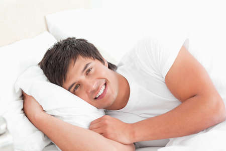 Man looking forward, smiling with his head resting on a pillow as he lies on the bed.