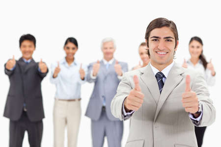 thumbsup: Close-up of a multicultural business team with their thumbs-up focus on a smiling man in foreground