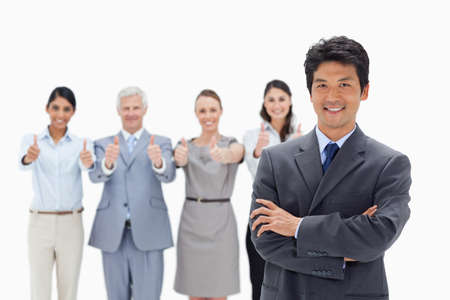 thumbsup: Close-up of a business team with their thumbs-up with a smiling Asian man crossing his arms in foreground LANG_EVOIMAGES