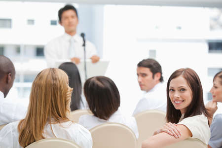 looking behind: Brown haired businesswoman happy while looking behind her during a speech