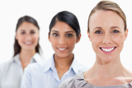 single line: Close-up of smiling businesswomen in a single line with focus on the first person against white background