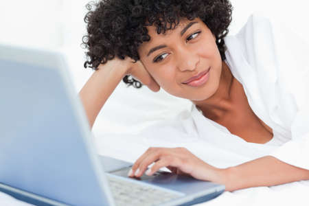 haired: Cute black haired woman lying on her bed with a laptop