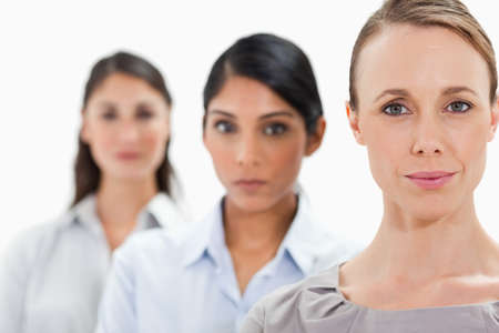 single line: Big close-up of businesswomen in a single line with focus on the first person against white background
