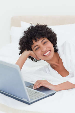 frizzy: Portrait of a frizzy smiling haired woman lying on her bed with her laptop