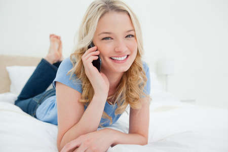 phonecall: A woman relaxing on the bed as she smiles looking forward while making a phonecall. LANG_EVOIMAGES