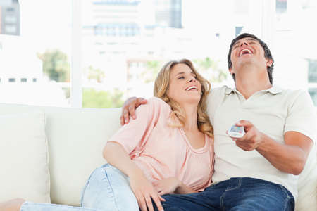 programme: A man and woman on the couch together laughing at a funny television programme.