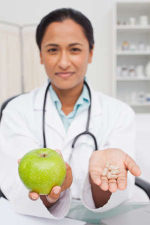 nutritionist: Relaxed nutritionist holding a delicious green apple and vitamins LANG_EVOIMAGES