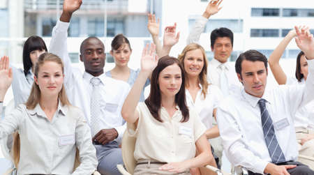arms above head: Colleagues raising their arms above their head as they sit in a group