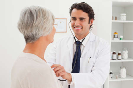 heart beat: Smiling young doctor taking mature patients heart beat